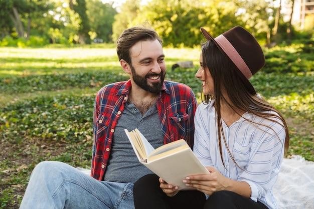 Radosna para mężczyzna i kobieta ubrani w ubranie codzienne czytające książkę podczas odpoczynku w zielonym parku