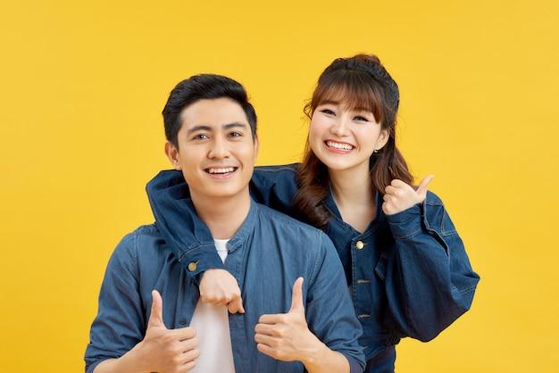 Radosna para pokazując kciuk do góry, podczas gdy mężczyzna piggybacking radosna kobieta odizolowana na żółtym tle