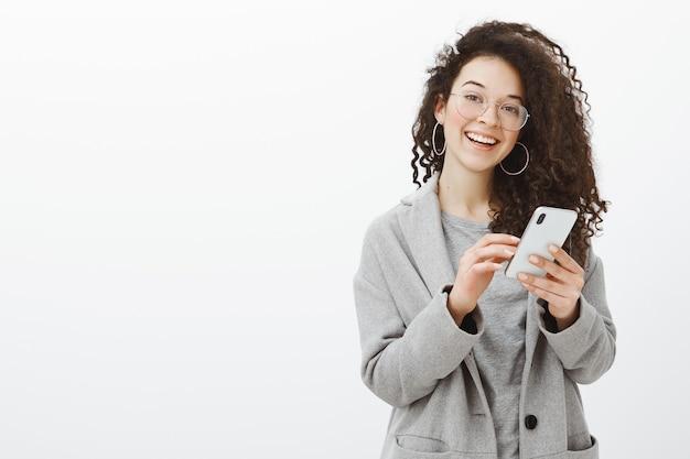 Radosna, pełna emocji młoda europejka w okularach i szarym płaszczu ze stylowymi okrągłymi kolczykami