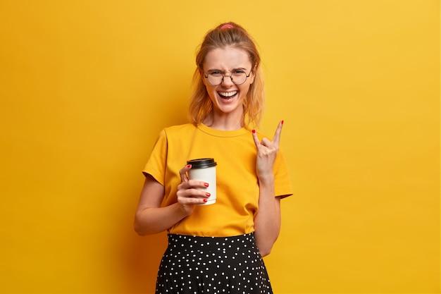 Radosna, pewna siebie zrelaksowana dziewczyna robi heavy metalowy znak, lubi rock, radośnie się śmieje, trzyma kawę na wynos, spędza wolny czas na dzikim koncercie, niesamowity festiwal muzyczny