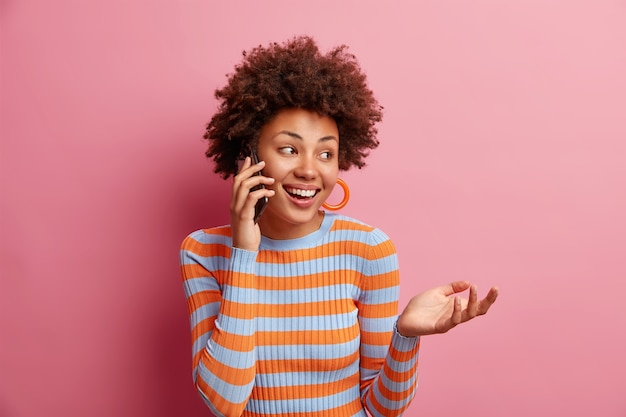 Radosna piękna afroamerykańska kobieta rozmawia przez telefon lubi rozmowę odwraca wzrok z uroczym uśmiechem trzyma rękę uniesioną do góry, nosi swobodny sweter w paski odizolowany na różowej ścianie, ma ciekawą rozmowę