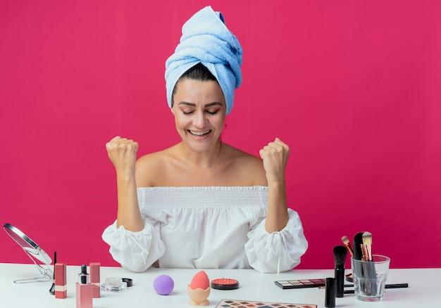 Radosna piękna dziewczyna owinięty ręcznikiem do włosów siedzi przy stole z narzędziami do makijażu podnosi pięści na różowej ścianie