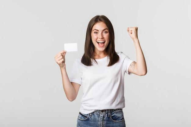 Radosna piękna dziewczyna pokazująca kartę kredytową i triumfująca, szczęśliwa pompka pięści, biała.
