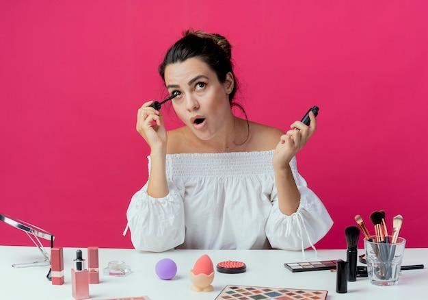 Radosna piękna dziewczyna siedzi przy stole z narzędziami do makijażu stosując tusz do rzęs na białym tle na różowej ścianie