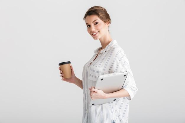 Radosna piękna kobieta pijąca kawę na wynos i trzymająca laptopa odizolowanego na białym tle