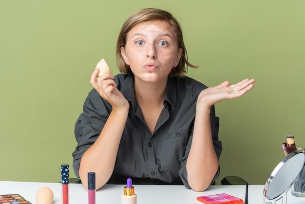 Radosna piękna kobieta siedzi przy stole z narzędziami do makijażu, stosując krem toniczny, trzymając gąbkę pokazując gest pocałunku, rozprowadzając dłoń