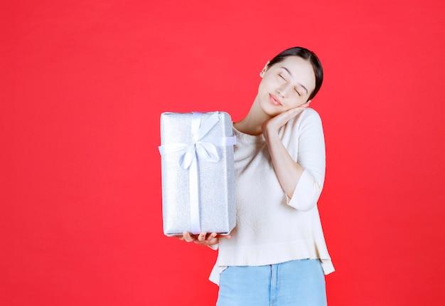 Radosna piękna kobieta trzyma pudełko i stoi na czerwonej ścianie