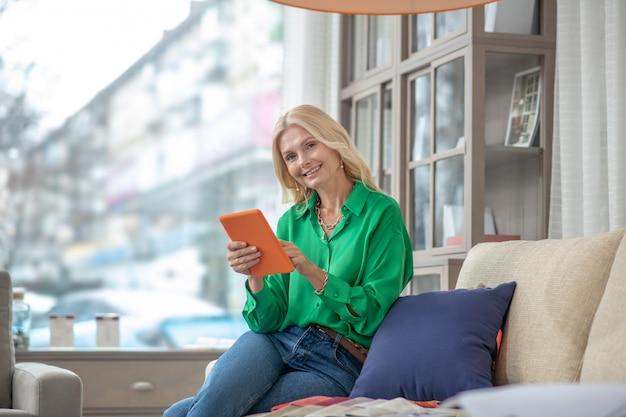 Radosna piękna kobieta z pomarańczową tabletką w dłoniach, siedząca na sofie w salonie meblowym, w znakomitym nastroju.
