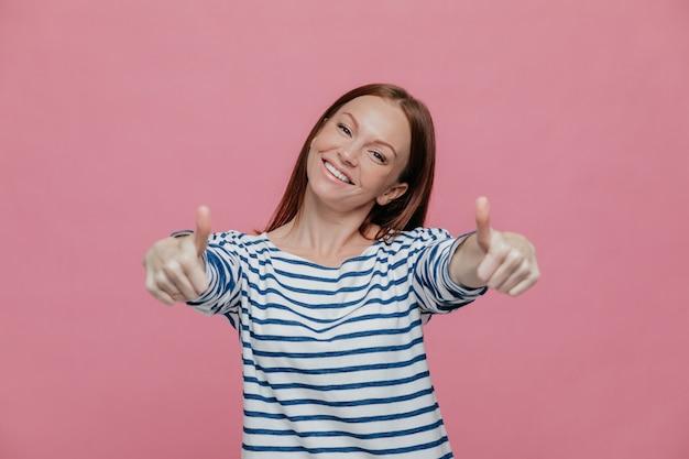 Radosna piękna młoda dama podnosi kciuki do kamery, pokazuje, że wszystko jest w porządku