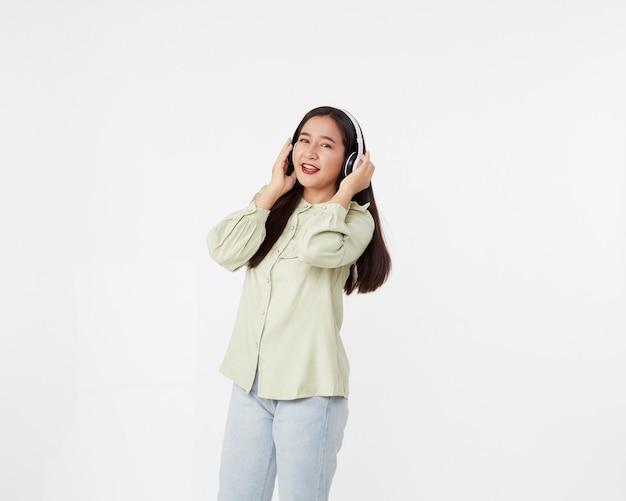 Radosna piękna młoda kobieta azji tańczy słuchanie muzyki w słuchawkach bezprzewodowych na białej powierzchni