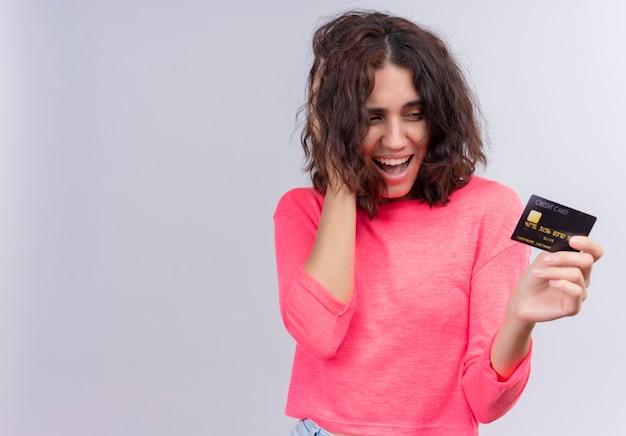 Radosna piękna młoda kobieta trzyma kartę i kładzie rękę na włosy na na białym tle białej ścianie z miejsca na kopię
