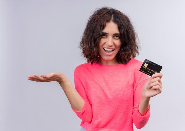 Radosna piękna młoda kobieta trzyma kartę i pokazuje emty rękę na odosobnionej białej ścianie