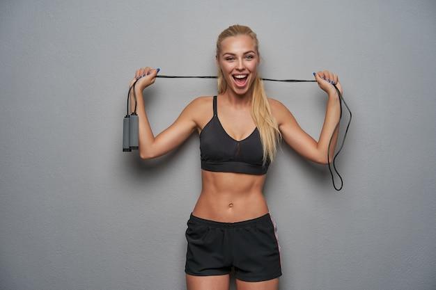 Radosna piękna młoda sportowa blondynka z fryzurą w kucyk trzymająca skakankę w uniesionych dłoniach i radośnie patrząc na aparat z otwartymi ustami, odizolowana na jasnoszarym tle