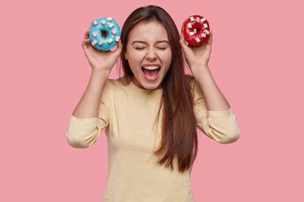 Radosna podekscytowana pani woła ze szczęścia, niesie dwa niebieskie i czerwone pączki, ma pokusę, by je zjeść, przestrzega diety, szeroko otwiera usta