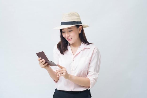 Radosna podróżująca kobieta jedzie na wakacje na białej koncepcji studia, podróży i turystyki
