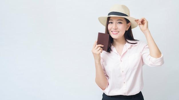 Radosna podróżująca kobieta jedzie na wakacje na białym tle koncepcji studia, podróży i turystyki