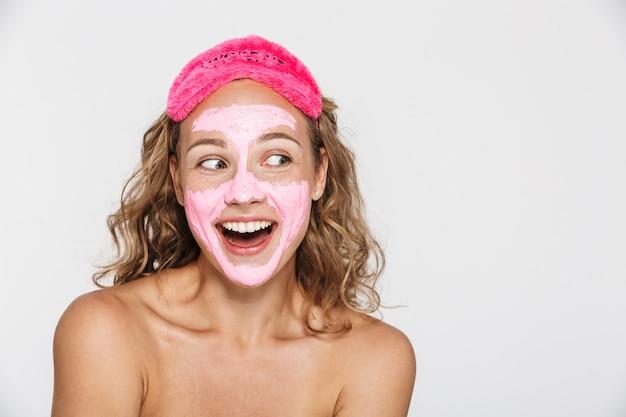 Radosna półnaga kobieta w twarzy i maskach do spania, śmiejąca się, patrząc na bok, odizolowana nad białą ścianą