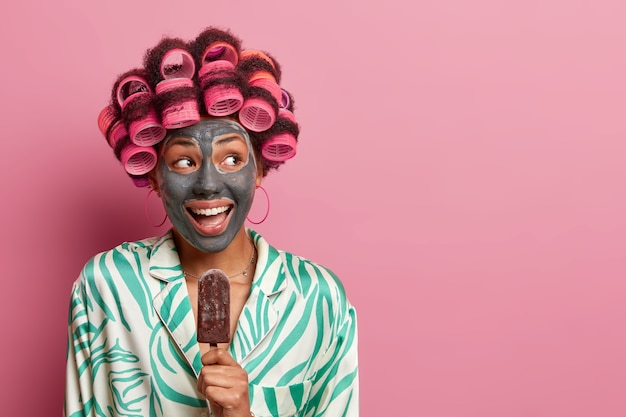 Radosna pozytywna kobieta nosi wałki do loków i maskę kosmetyczną, zjada pyszne lody czekoladowe, nosi swobodny szlafrok, radośnie patrzy na bok, odizolowana na różowym, pustym miejscu na kopię.
