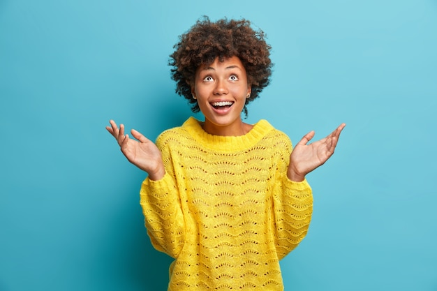 Radosna, pozytywna kobieta z cudownym, szczęśliwym wyrazem twarzy wygląda powyżej, trzyma dłonie uniesione w uśmiechu, ubrana w dzianinowy żółty sweter odizolowany na niebieskiej ścianie nie może uwierzyć, że marzenie się spełniło