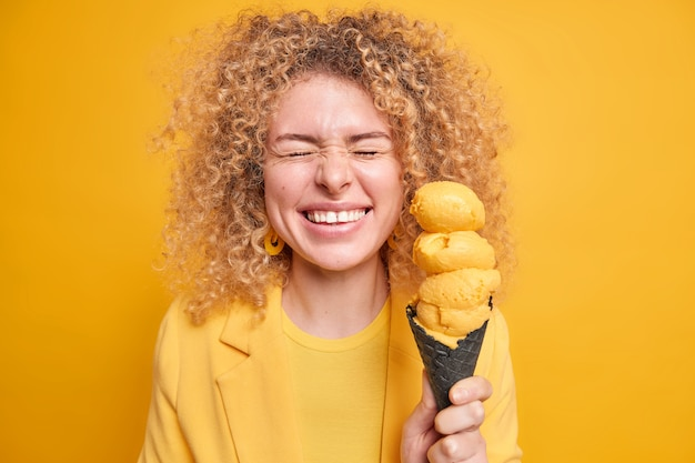 Radosna pozytywna kobieta z kręconymi włosami zamyka oczy od szczęścia uśmiecha się szeroko trzyma smaczne apetyczne lody o cytrynowym smaku w wafelku wyraża szczere, autentyczne emocje. strzał monochromatyczny.