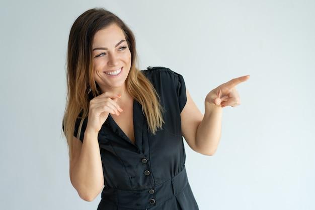 Radosna pozytywna młoda kobieta śmia się i wskazuje na boku.