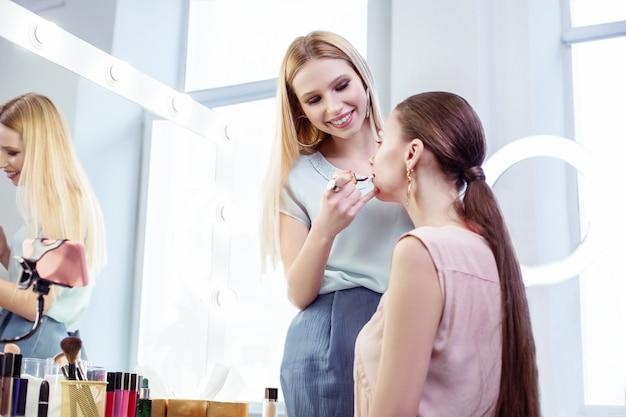Radosna pozytywna wizażystka uśmiechnięta podczas nakładania makijażu dla swojego klienta