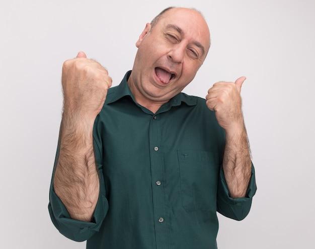 Radosna przechylająca się głowa z zamkniętymi oczami mężczyzna w średnim wieku ubrany w zieloną koszulkę pokazujący gest tak na białym tle na białej ścianie
