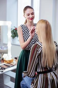 Radosna, przyjazna kobieta uśmiecha się do swojego klienta podczas oczyszczania skóry