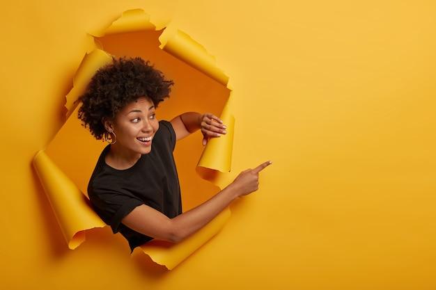 Radosna, przyjaźnie wyglądająca uśmiechnięta dziewczyna wskazuje na bok ze szczęśliwym wyrazem twarzy, zębatym uśmiechem, zadowolona z pokazania niesamowitej reklamy