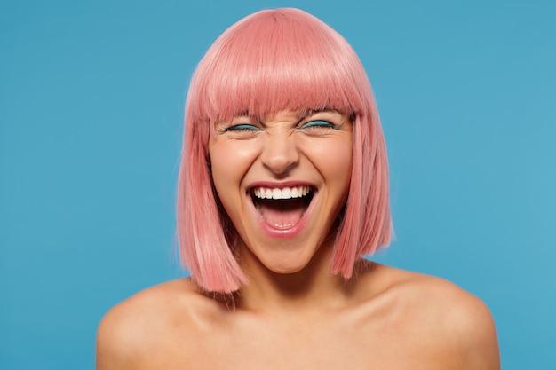 Radosna, przyjemnie wyglądająca młoda kobieta z krótkimi różowymi włosami, ubrana w kolorowy makijaż, pozując na niebieskim tle, trzymając oczy zamknięte, uśmiechając się radośnie z szeroko otwartymi ustami