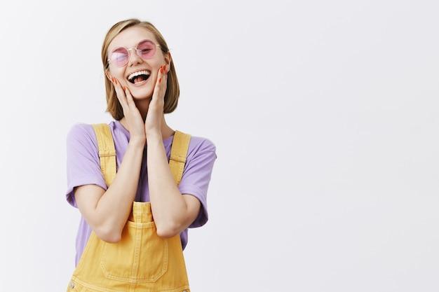 Radosna przystojna młoda kobieta w okularach przeciwsłonecznych i letnich ubraniach, śmiejąca się i wzruszająca twarz