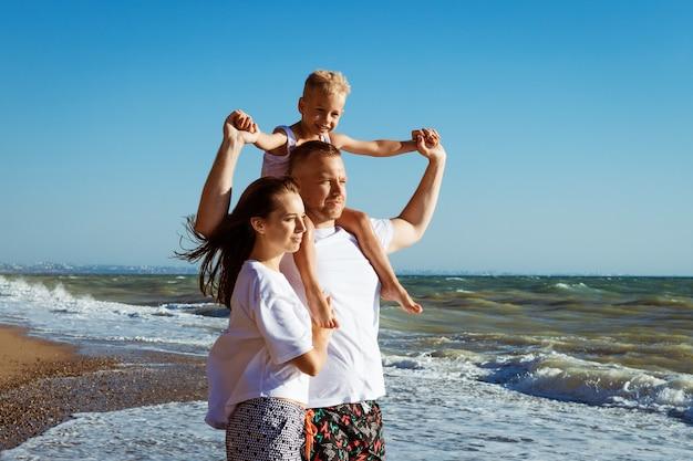 Radosna rodzina na plaży ludzie bawią się widok lato wakacje ojciec matka i dziecko przed błękitnym morzem i niebem koncepcja podróży wakacje