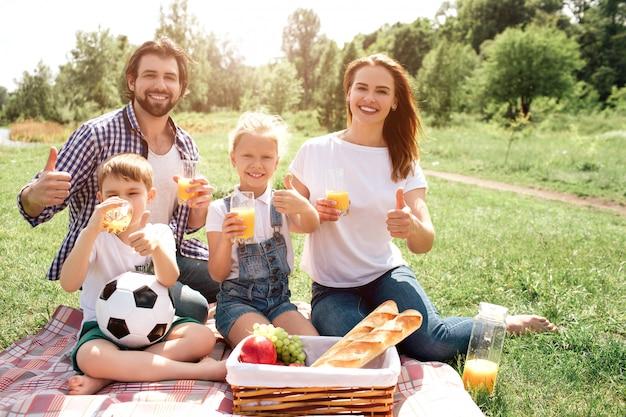 Radosna rodzina siedzi na kocu i patrzy. oni się uśmiechają. każdy z nich ma szklankę z sokiem pomarańczowym. pokazują podobny symbol.