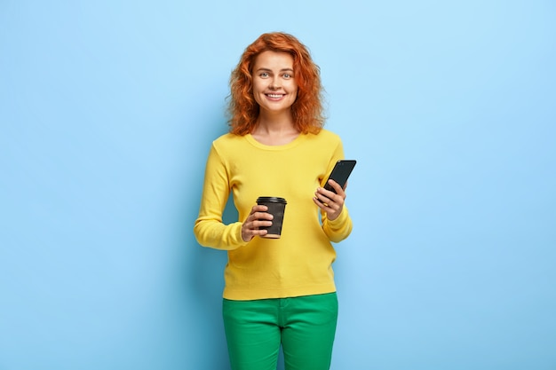 Radosna rudowłosa uczennica trzyma w rękach nowoczesny telefon komórkowy, lubi rozmawiać z przyjacielem za pośrednictwem aplikacji