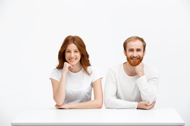 Radosna rudzielec, mężczyzna i kobieta pozuje z ręką na brodzie