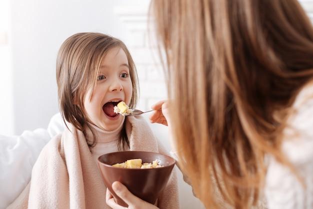 Radosna śliczna mała dziewczynka je śniadanie z matką i wyrażając radość podczas wspólnego odpoczynku