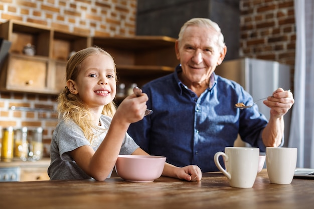 Radosna śliczna mała dziewczynka siedzi z dziadkiem, delektując się śniadaniem w kuchni