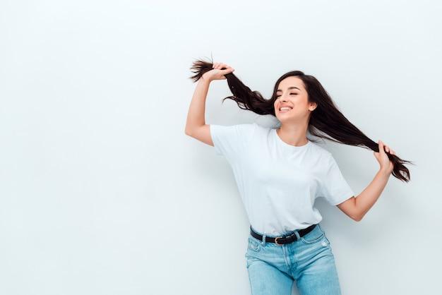 Radosna śmieszna kobieta trzyma włosy jak dwa kucyki