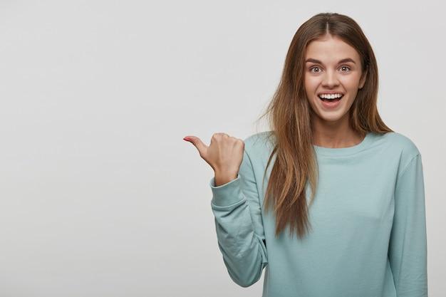 Radosna śmieszna nastoletnia kobieta pokazuje pustą przestrzeń kopii z jej kciukiem palcem
