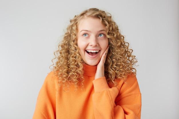 Radosna śniąca, kręcona blondynka, uśmiecha się i przykłada dłoń do twarzy
