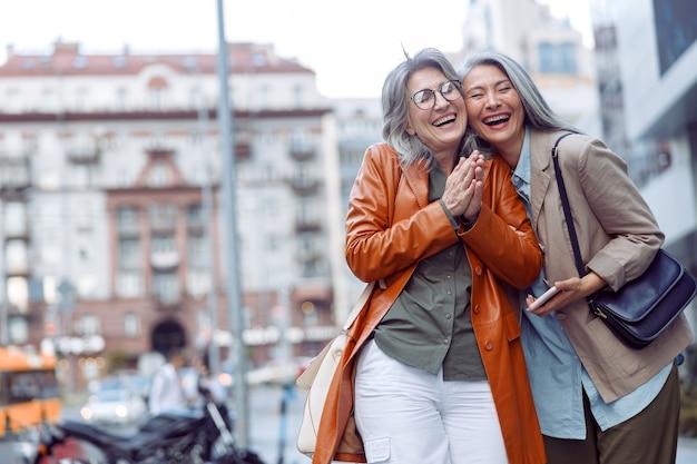 Radosna starsza kobieta i azjatycki towarzysz trzymający stojak na smartfona na nowoczesnej ulicy miasta