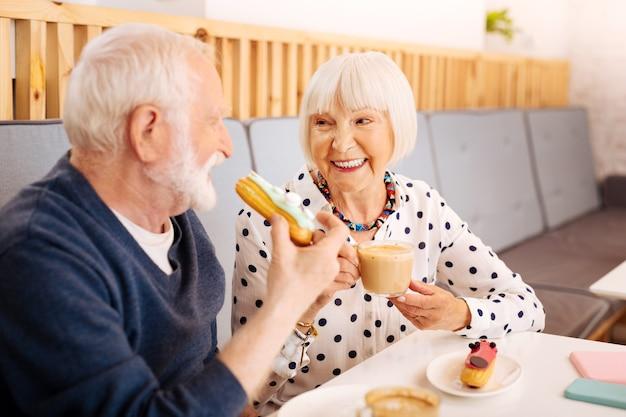Radosna starsza kobieta rozkoszująca się kawą i starszy mężczyzna gryzący eclair