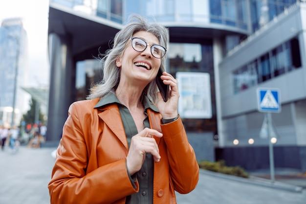 Radosna starsza pani z siwymi włosami rozmawia przez telefon na nowoczesnej ulicy miasta