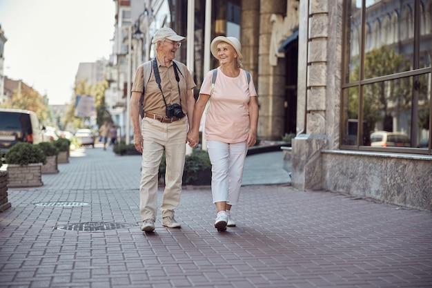 Radosna starsza para turystów spacerująca ramię w ramię po centrum miasta
