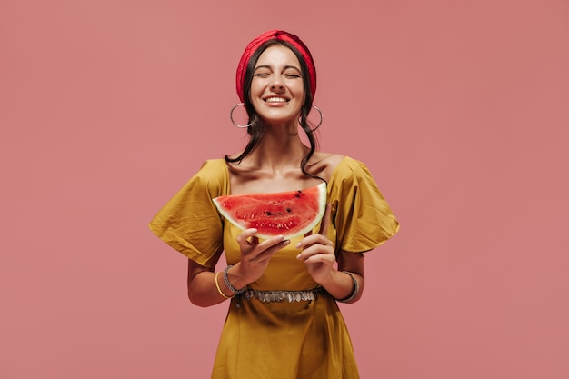 Radosna stylowa dama z fajną fryzurą w jasnej bandanie, srebrnych okrągłych kolczykach i żółtej sukience pozuje z zamkniętymi oczami