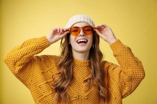 Radosna stylowa kaukaska dziewczyna korzystająca ze światła słonecznego zimowy ośrodek narciarski noszący okulary przeciwsłoneczne kapelusz ciepły sweter zabawy uśmiechający się dotykając okularów, wyrażający zabawny, szczęśliwy nastrój żółte tło