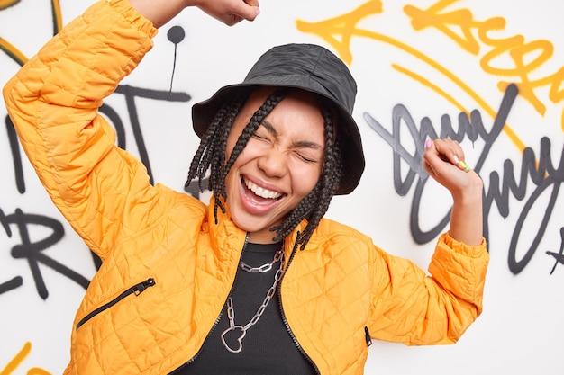 Radosna stylowa nastolatka unosi ramiona tańczy na tle kolorowych miejskich graffiti ściana się bawi nosi modne ciuchy porusza się beztrosko zamyka oczy szeroko się uśmiecha