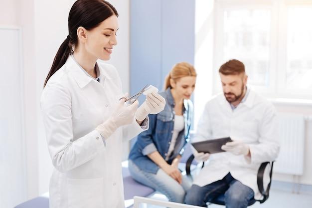 Radosna, sympatyczna młoda kobieta trzymająca nożyczki i odcinająca kawałek bandaża podczas asystowania w gabinecie lekarskim