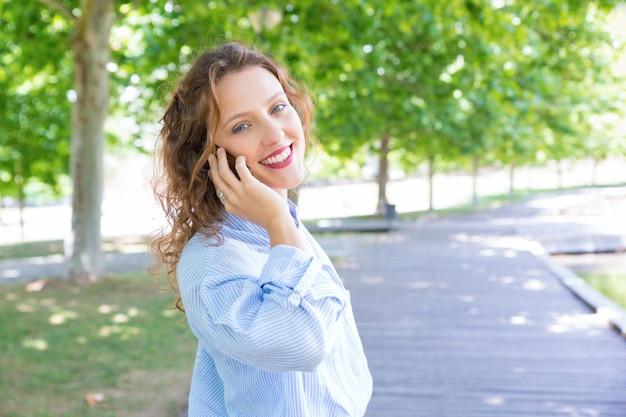 Radosna szczęśliwa dziewczyna mówi na telefonie komórkowym
