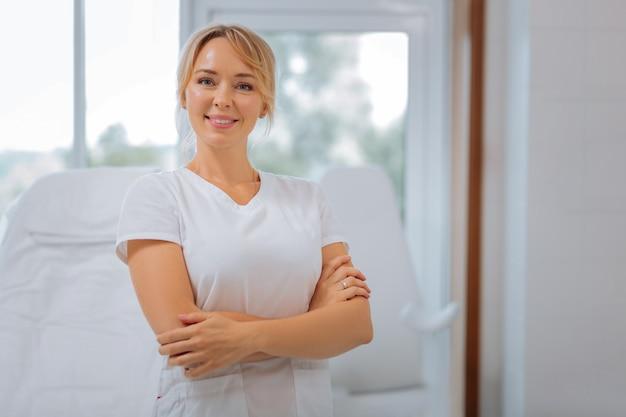 Radosna szczęśliwa kobieta stojąca na krzyżu wręczona podczas pracy jako kosmetyczka